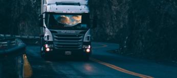 Truck driving on darkened road